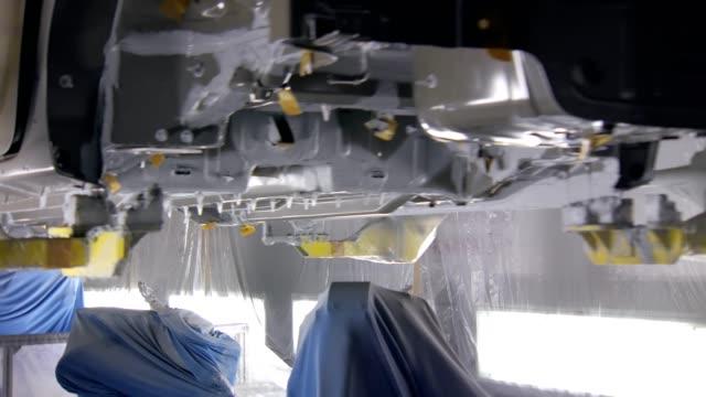 vídeos de stock e filmes b-roll de robots are painting car body in a automobile factory , moving under auto - matéria corante