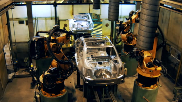 robots are welding the car body, making car body on a automobile factory video