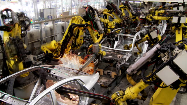 robots collect and weld car bodies at the car factory - automatico video stock e b–roll