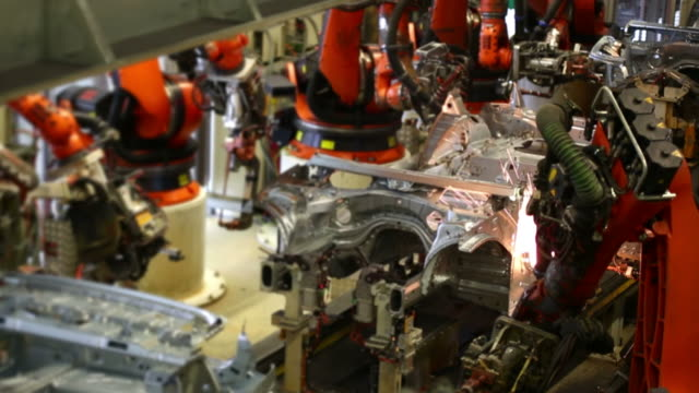 T/L Robots Welding On Car Body Robots welding on car body time lapse.   Shot with LEICA Apo-Summicron-R 180mm f/2 lens.   vehicle part stock videos & royalty-free footage