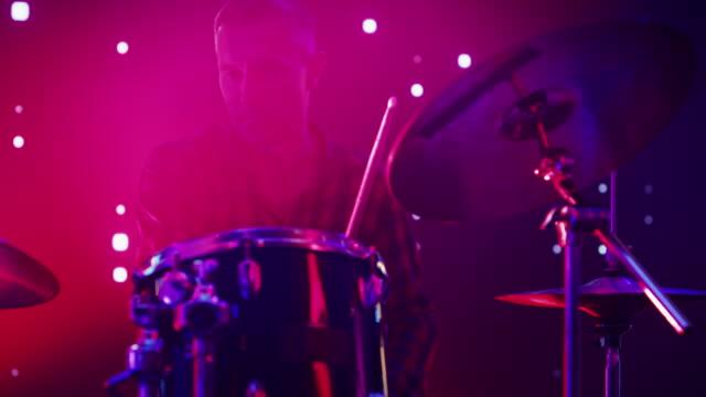 rock band utför på en konsert i en nattklubb. närbilder porträtt av en trummis spelar trummor. live music party framför bright colorful strobing lights på scenen. - gitarrist bildbanksvideor och videomaterial från bakom kulisserna