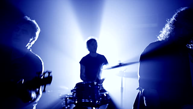 Rock band performing on stage Concert rock band performing on stage with singer performer, guitar, drummer.  Music video punk, heavy metal or rock group.  Slow motion instrument playing band of men. rock music stock videos & royalty-free footage