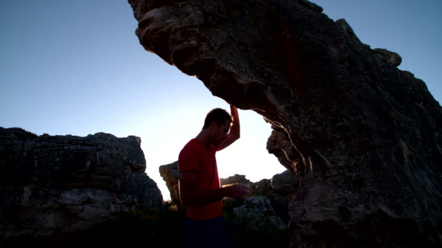 Rock climber applying chalk to hands in preparation for climbing video