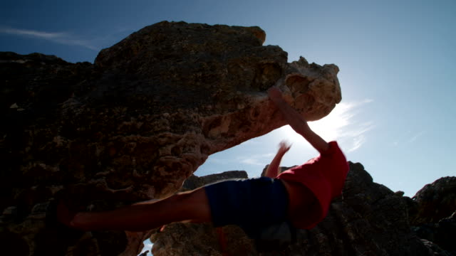 Rock climber bouldering outdoors on mountain in nature video