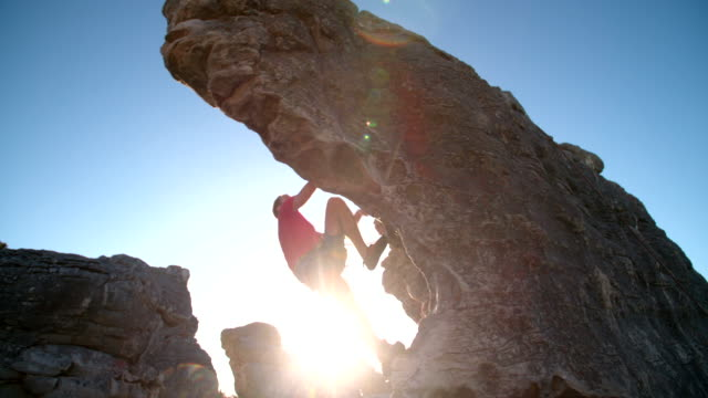 Rock climber bouldering outdoors on mountain in nature Rock climber holding on to rock overhang as he boulders up mountain. He is strong and focused. rock music stock videos & royalty-free footage