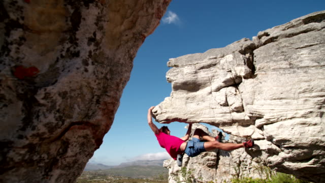 Rock climber holding to boulder and focused on route Bouldering man climbing up rock. He has his grip and hangs in overhang. rock music stock videos & royalty-free footage
