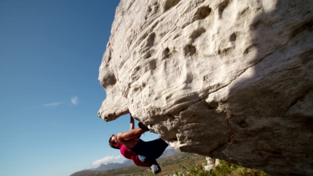 Rock climber holding to boulder and focused on route Low angle of strong rock climbing man hanging free on rock with sunflare against blue sky. boulder rock stock videos & royalty-free footage