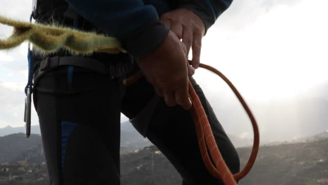 Rock climber organizes gear on cliff summit