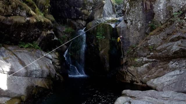 ロック ・ クライマーが滝のプランジ プールに突入します。 - 自然旅行点の映像素材/bロール