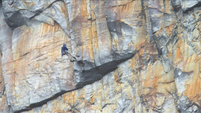 Rock climber rappelling down the side of a mountain in Du Toit's Kloof, South Africa video