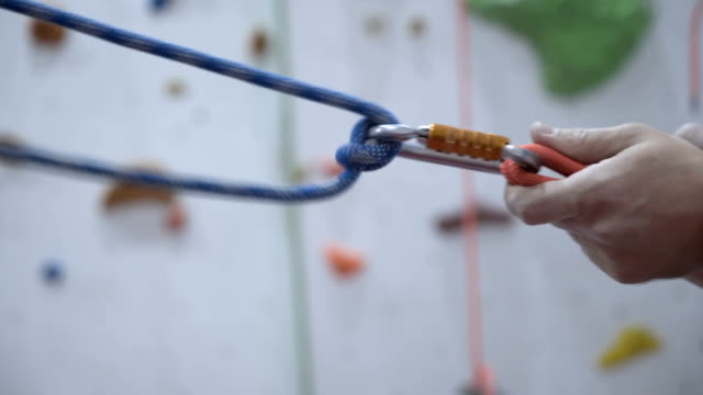 A rock climber tie a bowline knot for insurance
