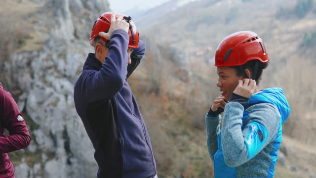 Rock climbers adjusting safety helmets