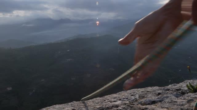 vídeos de stock e filmes b-roll de rock climbers hands haul in rope from cliff edge - puxar