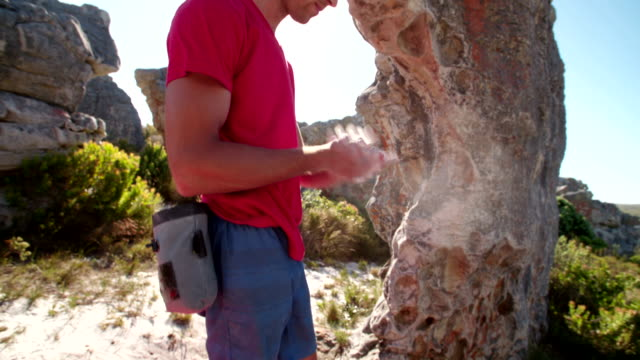 Rock climber's hands rubbing chalk in preparation for climbing ascent video