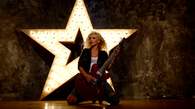 rock girl playing her electric guitar on knees, slow motion video