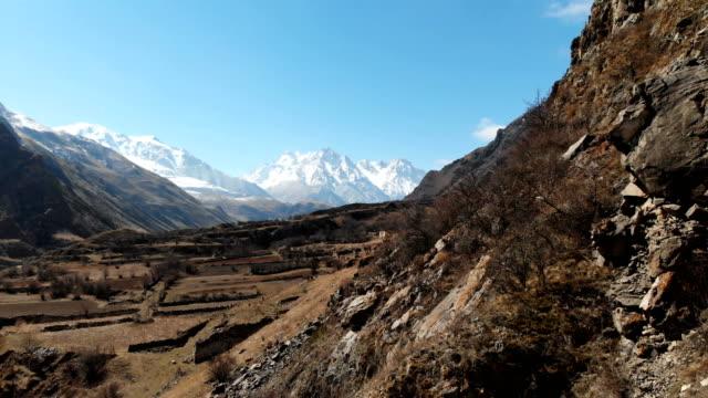 rock i bergen i övre balkarien. aerial utsikt över ravinen med en grusväg och ett berg klippor i bergen i kaukasus. - stenmur bildbanksvideor och videomaterial från bakom kulisserna
