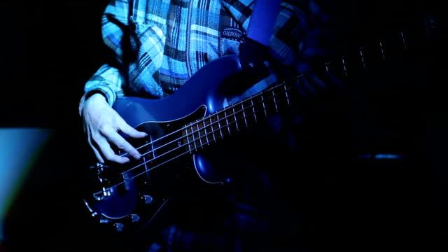 Rock musician playing bass guitar on concert video
