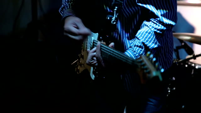 Rock musician playing electrical guitar on concert video