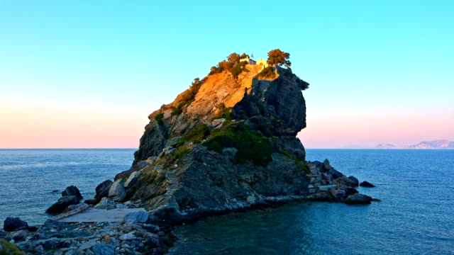 Rock with Agios Ioannis church on Skopelos island at sunset video