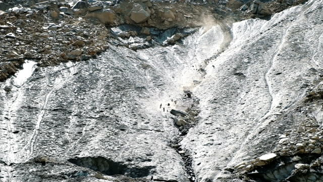rockfall in the mountains, stones fall down from the glacier, slow motion - pietra roccia video stock e b–roll