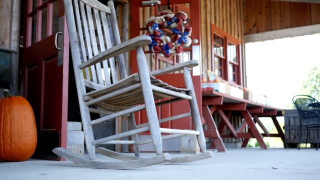 rocking chair gently rocking on country front porch - oscillare video stock e b–roll