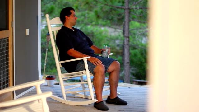 sedia a dondolo uomo - portico video stock e b–roll