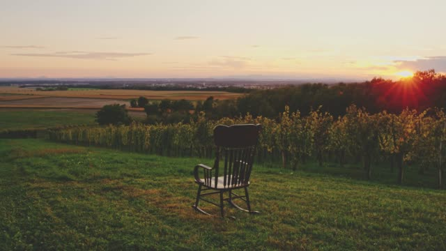 Rocking chair rocking in lawn overlooking idyllic rural sunset landscape, real time 4K Rocking chair rocking in lawn overlooking idyllic rural sunset landscape. WS, real time. rocking chair stock videos & royalty-free footage