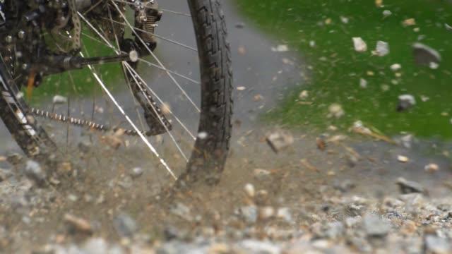 rocks flying when cyclist breaks hard on gravel road slow motion - ghiaia video stock e b–roll