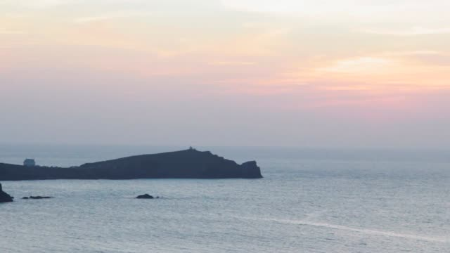 Rocky Headland juts out into the deep sea at dusk video