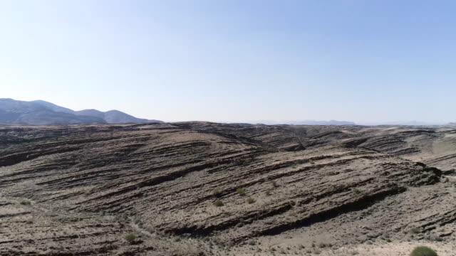 vídeos de stock e filmes b-roll de rocky landscape with reddish soil. planet surface - surrealismo