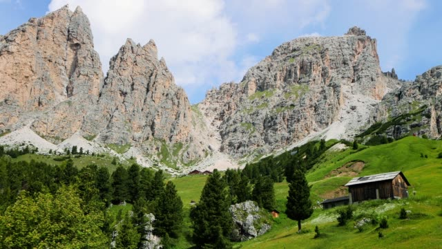 Rocky mountains with a cabin in the valley in Italy. Beautiful landscape in a natural park - time lapse 4K