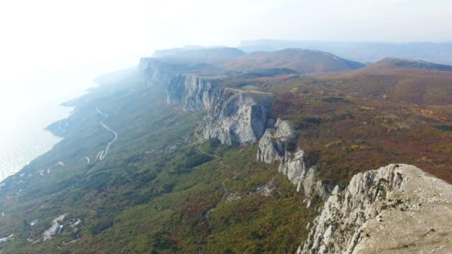 vídeos de stock, filmes e b-roll de antena: montanhas rochosas com florestas verdes e o mar azul abaixo - multicóptero