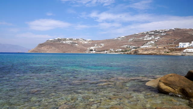 Rocky shore of the Mediterranean Sea with pebbles and mountain on background. Rocky shore of the Mediterranean Sea with pebbles with mountains and white local houses in the background. Greece, the island of Mykonos. aegean islands stock videos & royalty-free footage