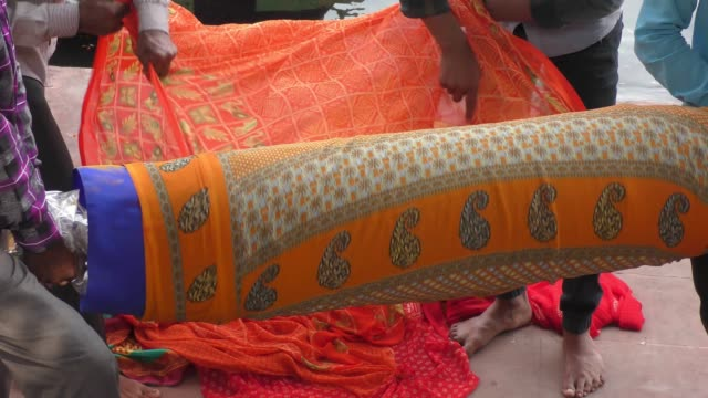 roll of colorful long cloth of saree being unstacked by hands. - sari filmów i materiałów b-roll