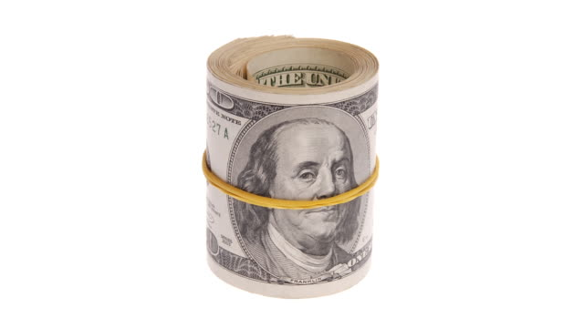 roll of money rotates on a white background. roll of bills. roll of dollar bills. - rotolo video stock e b–roll