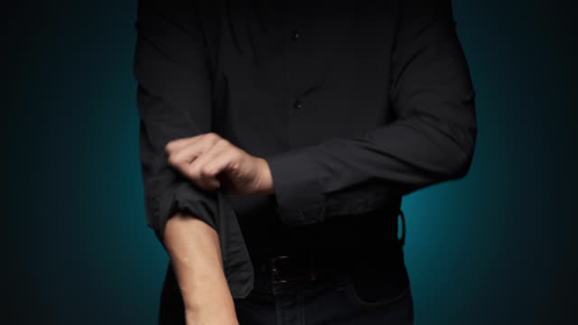 Roll Up The Sleeves Close up of a man rolling up his sleeves, getting ready to work under dramatic lighting. sleeve stock videos & royalty-free footage
