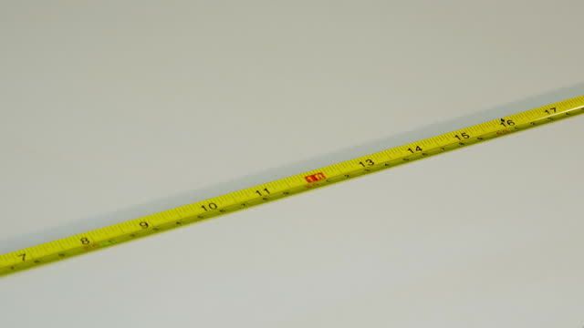 Roll up the yellow measuring tape. video