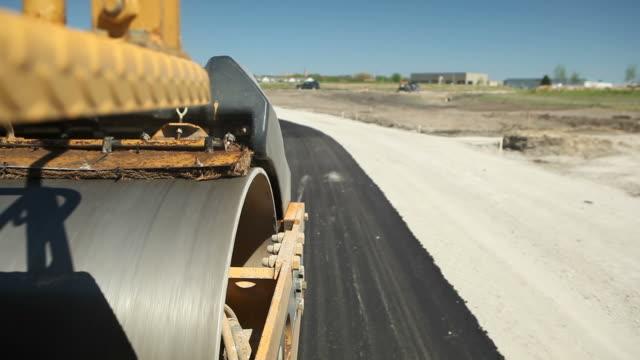 roller pressmaschine auf frischen asphaltstraße - asphalt stock-videos und b-roll-filmmaterial
