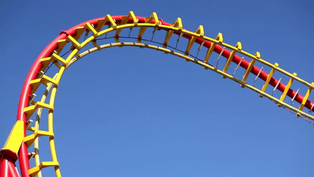 rollercoaster against blue sky - roller coaster stock videos & royalty-free footage