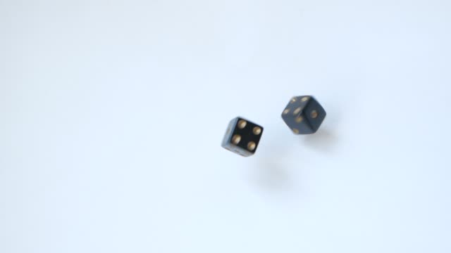 rolling a six and a five with a pair of black gambling dice on a table in slow motion - feltro video stock e b–roll