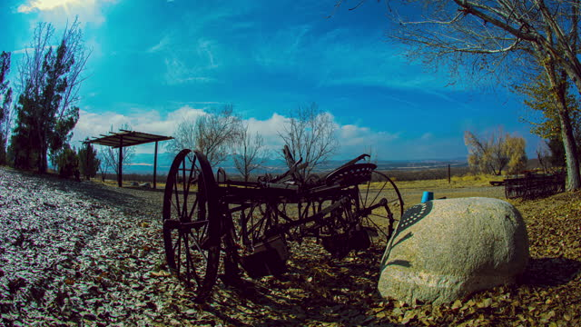 Rolling clouds over farmland with old, rusty plow