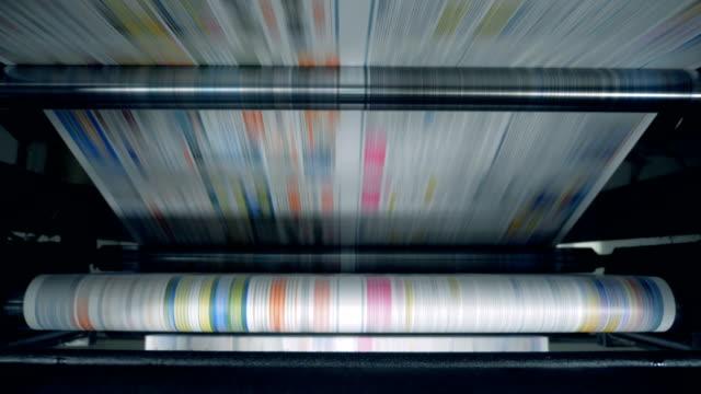vidéos et rushes de la machine de roulement relocalise le papier imprimé coloré - presse
