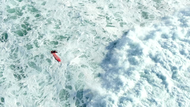 rolling ocean wave covers surfing person on red surfboard - vídeo