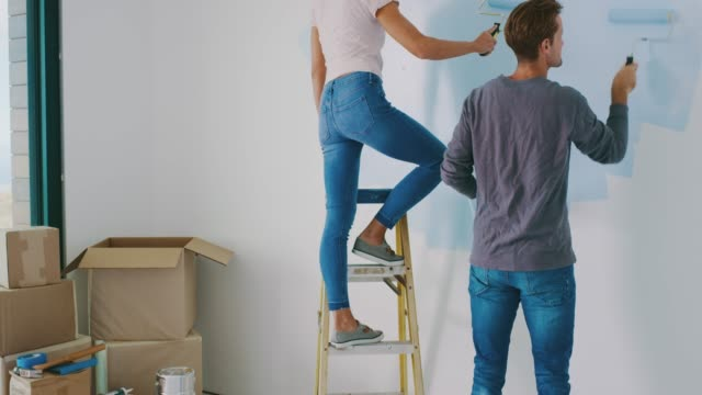 Rolling on the next layer together Cute couple painting wall in new home and kissing, happy new homeowners, home painting renovation stock videos & royalty-free footage