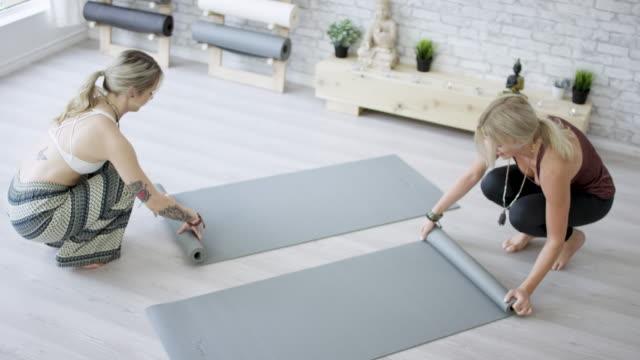 rolling up yoga mats - materassino ginnico video stock e b–roll