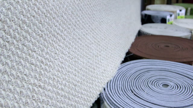 Rolls of carpets in retail flooring store video