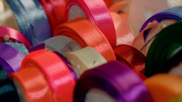 직물 상점에서 여러 가지 빛깔된의 실크 리본 롤 - ribbon 스톡 비디오 및 b-롤 화면