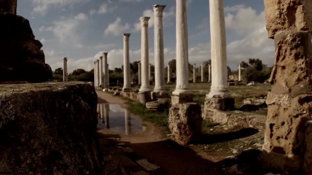 Roman agora white columns reflections in water blue sky with clouds antique town Salamis east Cyprus Famagusta video