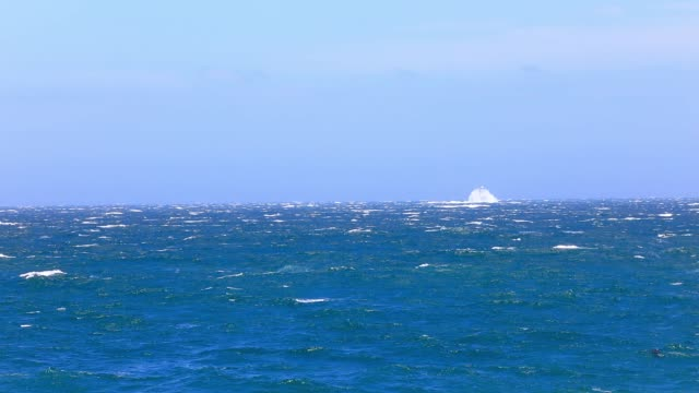 Roman Rock Lighthouse in False Bay Cape Town on a windy day with big rough waves