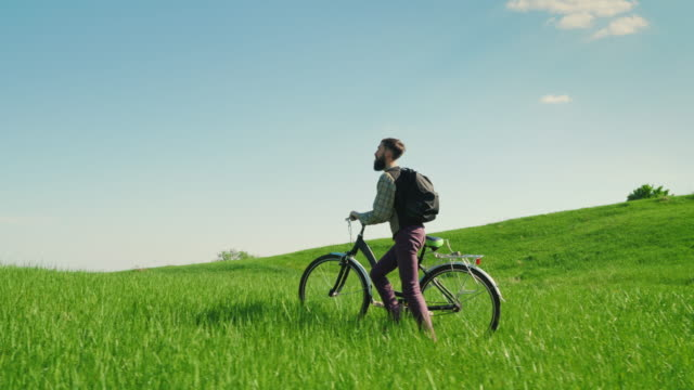 Romance of travel and tourism. A young man drives a bicycle along the green hills in a picturesque place video